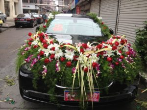 A car outside a florist getting ready for a wedding.